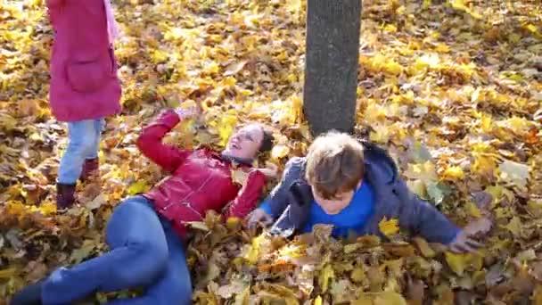 Matka a děti leží na spadané listí