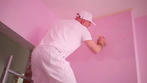 Malíř v bílém oblečení a chrániče kolen díla