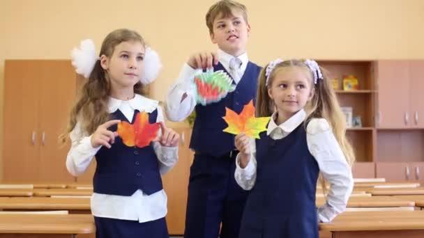 Zwei Mädchen und ein Junge stehen im Klassenzimmer