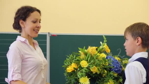 Fiú bemutatja csokor virág tanár
