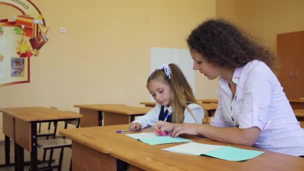 Girl sits at school desk with teacher