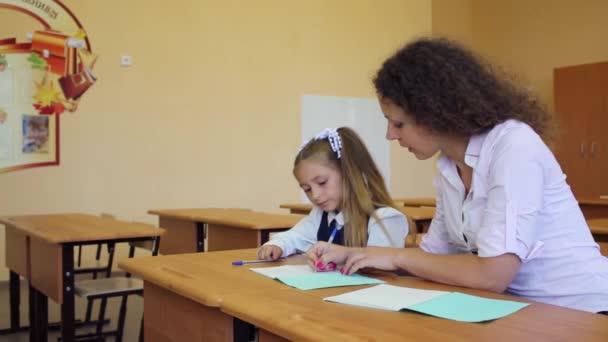 Dívka sedí na lavici ve škole s učitelem