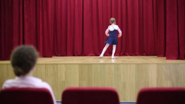 Žena při pohledu na tančící dívky na pódiu