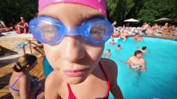 Little girl in goggles near pool