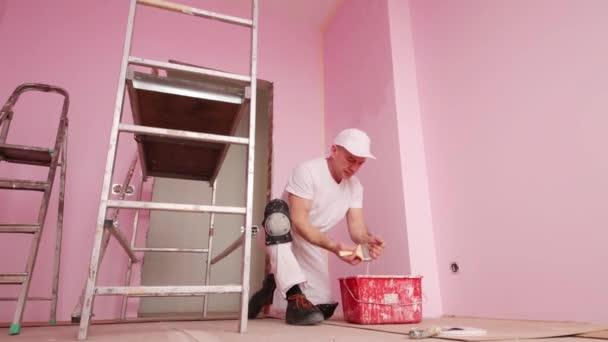 Maler in weißer Kleidung wäscht Pinsel