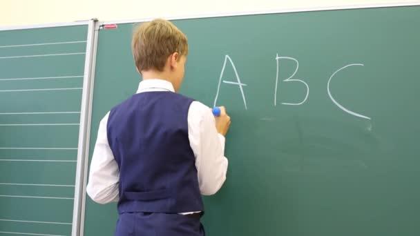 Chlapec stojí poblíž tabule v učebně