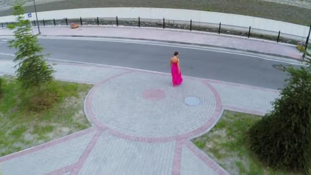 Žena v růžových šatech chodí