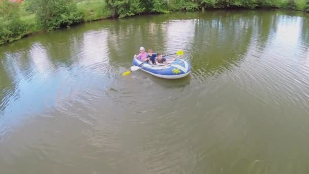Three kids on inflated boat by pond