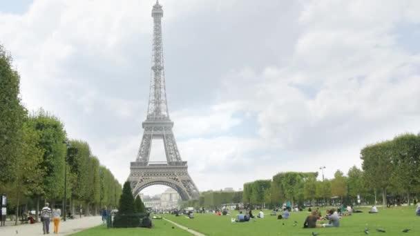 People relax near Eiffel Tower.