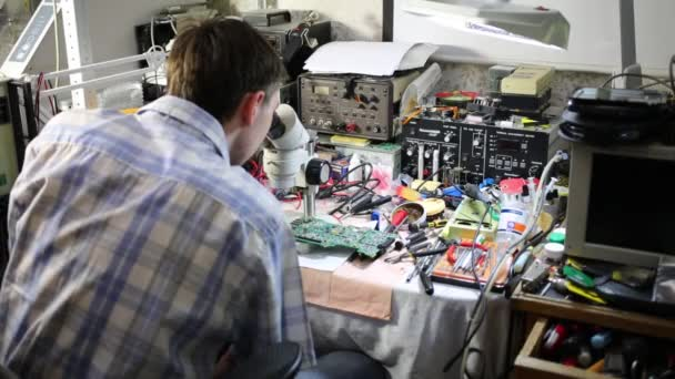 Man looks at motherboard through microscope among tools