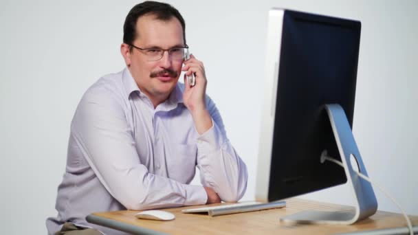 Employee sits at desk with computer and talks on mobile phone