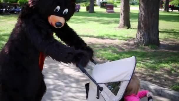Actor in bear suit perambulates baby
