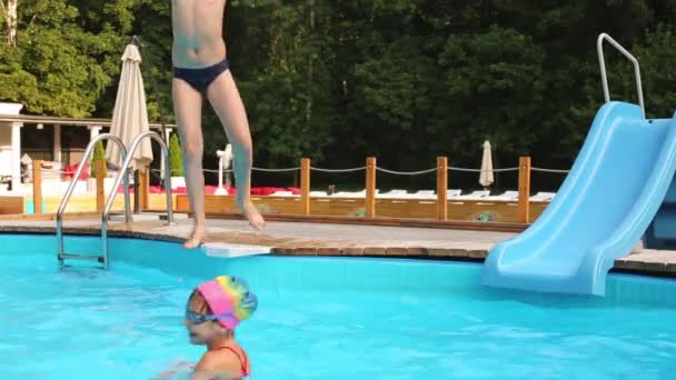 boy jumps in swimming pool to sister