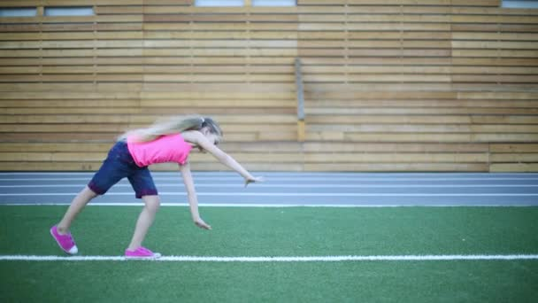 Girl in pink tumbles on green grass