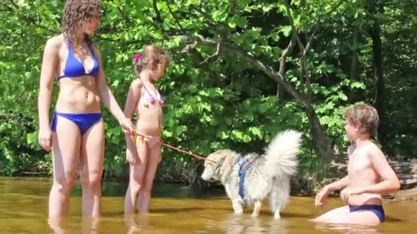 Mutter und zwei Kinder mit Hund im Wasser