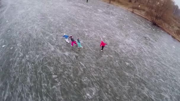 Quattro bambini pattinaggio su stagno ghiacciato