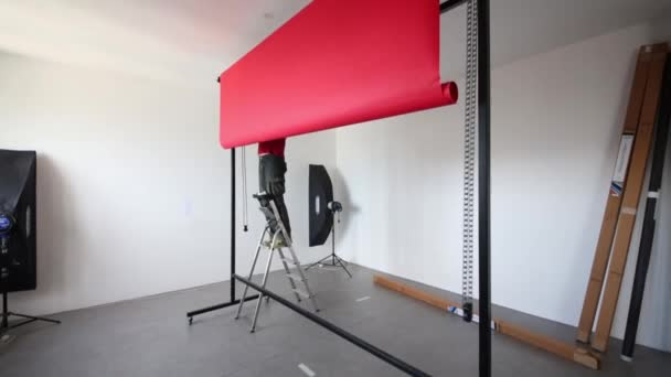 Man installs red background in studio