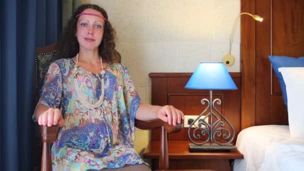 Hezká žena sedí v hotelovém pokoji