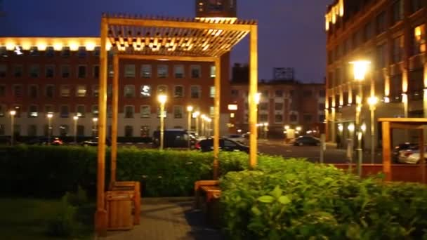 Altán, zelené křoví a budovy v noci