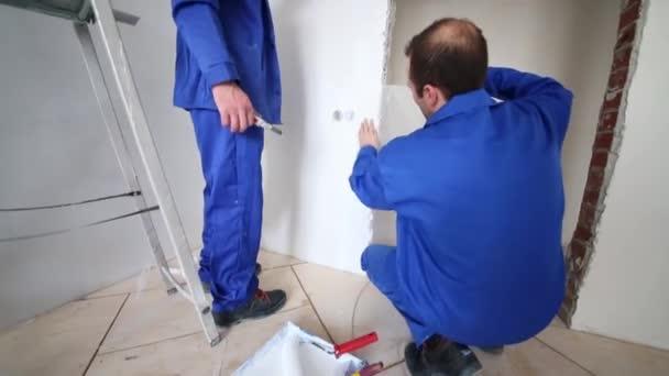 Dělníci lepidla na kus laminát na stěnu za dveřmi