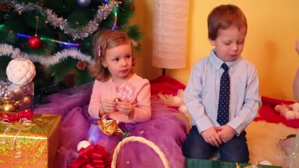 Little girls and boy near christmas tree