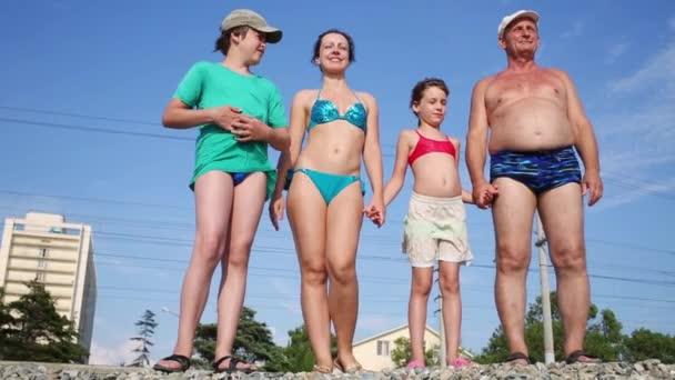 Rodina v plavkách stojí na štěrku