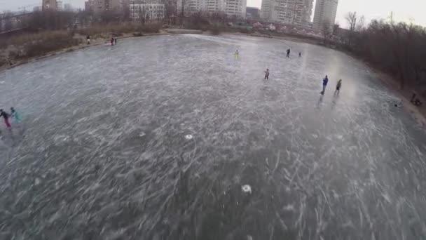 Children skating on icy pond