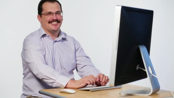man with mustache sits at table with computer and laughs