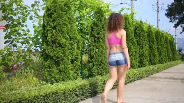 Žena v šortkách prochází uličkou