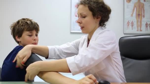 Ženský lékař klade na manžetu