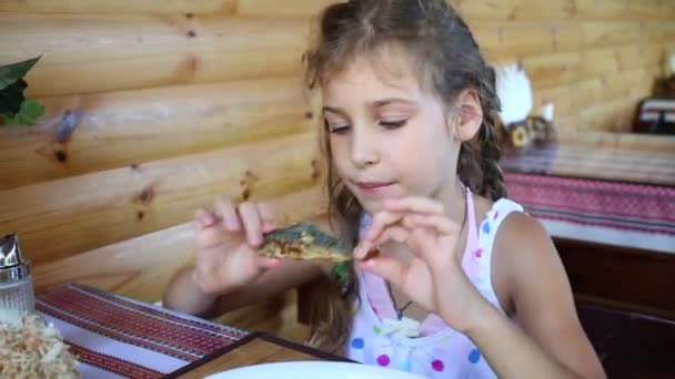 Little girl eats grilled fish