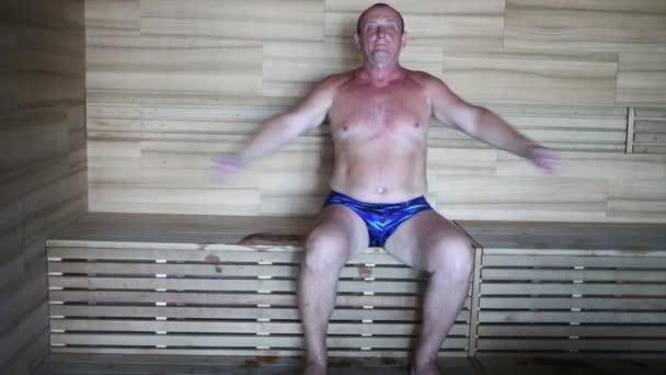 muž sedí na lavici v sauně