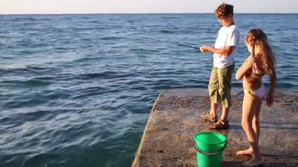 Boy with rod fishing in sea on pier