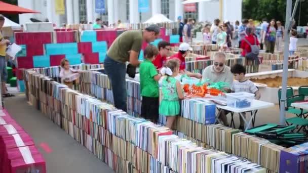 people walk along maze of books