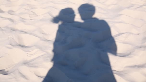 Male and female shadows on sand