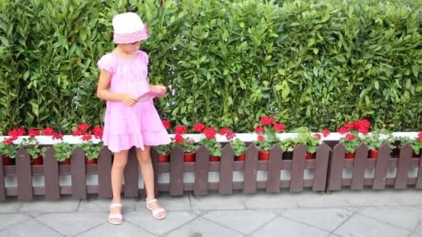 Bambina graziosa che si leva in piedi vicino al cespuglio