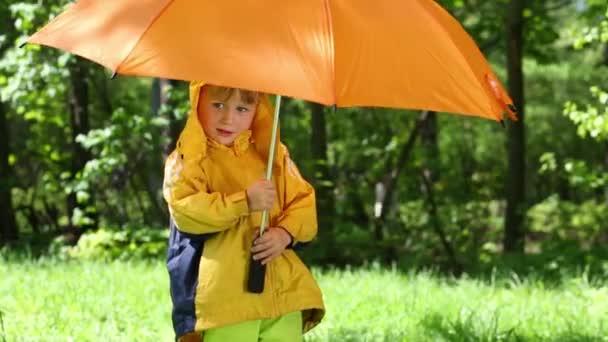 Lächelnder Junge mit Regenschirm steht auf Rasen