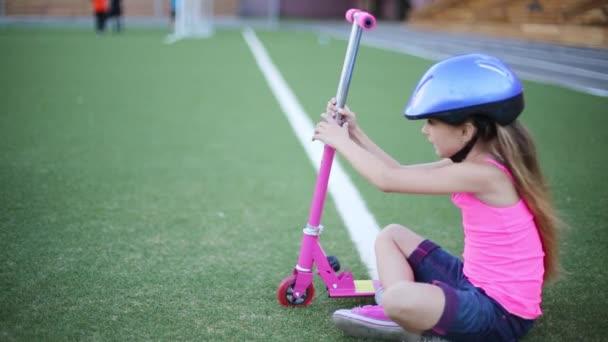 Dívka v helmě sedí s koloběžkou