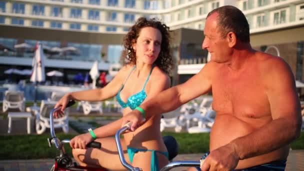 Badpak Voor Ouderen.Vrouw In Zwembroek En Ouderen Man Zit Op De Fiets Stockvideo