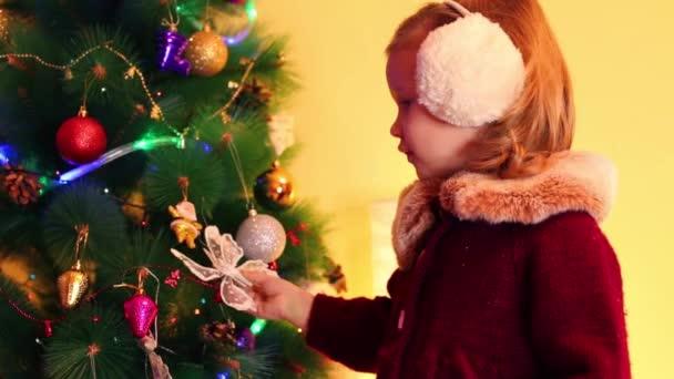 kleines Mädchen in der Nähe des Weihnachtsbaums