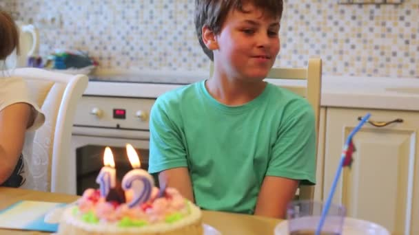 Il ragazzo si siede al tavolo con torta di compleanno