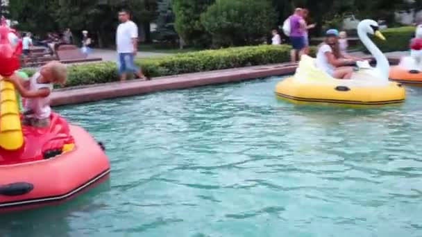 People on inflatable boats in pond