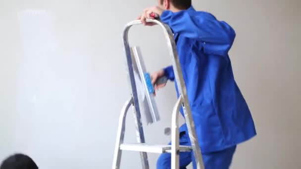 Muž dá žebřík, vyleze na něj a vyhladí laminátu