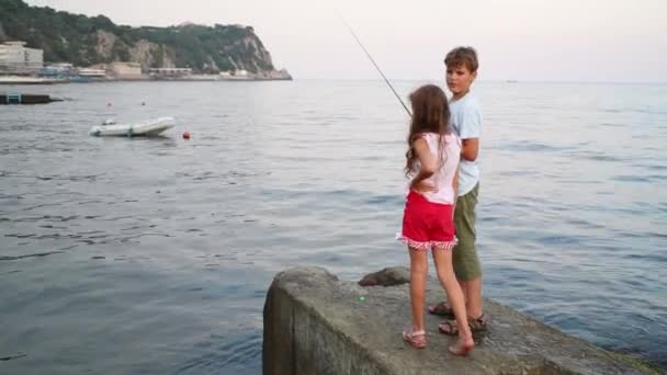 Chlapec a dívka s rod rybolov v modrém moři