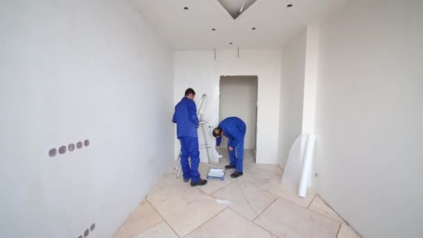 Worker apply the glue by roller on the wall next to the doorway