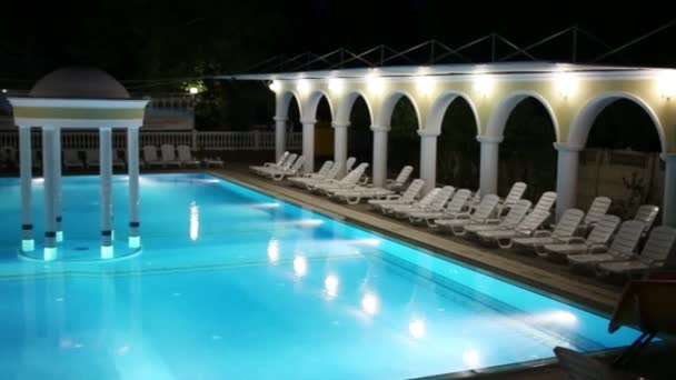 Empty swimming pool with loungers and rotunda