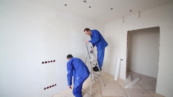 Mann schneidet überschüssiges Glasfaser, nächster Mann schmiert Klebstoff an die Wand
