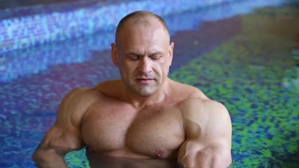 Bodybuilder strapaziert Muskeln im Wasser