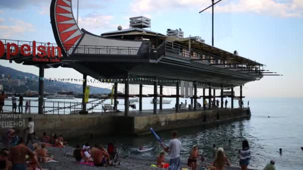 People rest near pier with cafe