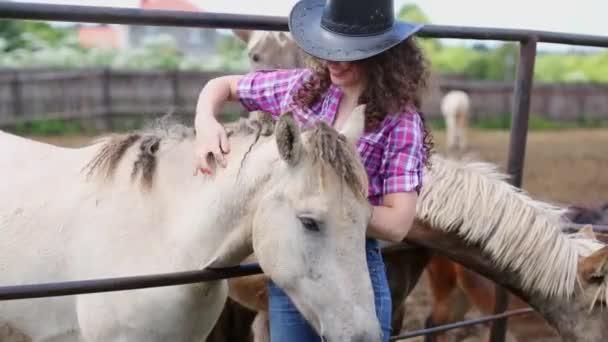 Lockige Frau streichelt Pferd